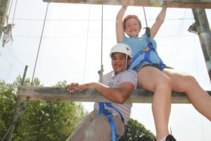Male and female P-TECH students in climbing gear at the ropes course of HVCC