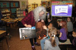 Museum Educator Naomi Meyer shows School 14 students artwork by Victor Ekpuk
