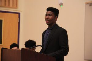 Male student stands at podium to debate raising the minimum wage.