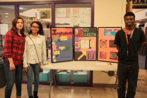 Three P-TECH students pose for a photo in front of their project display