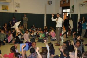 Principal Roy Stiles and room full of students raise their hands