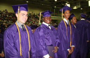 Three Troy high school graduates in cap and gown.