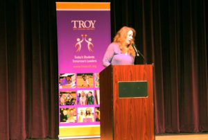 Nancy Jo Sales speaking behind a podium on stage at Troy Middle School.