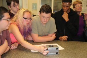 Students examining a piece of equipment at Simmons Machine Tool