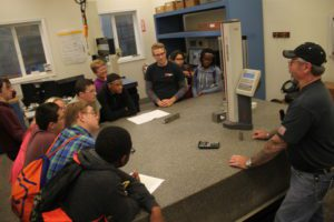 Students standing around a table learning about Simmons Machine Tool