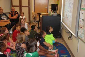 Students and parents watch the slideshow they made for their recycling project