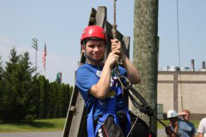 Male student in helmet and harness as he prepares for the ropes course