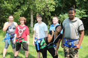 Students in harnesses smile for the camera