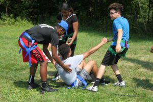 Students helping another student up off the ground