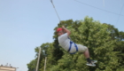 Male student in helmet and harness swinging through the air at the ropes course of HVCC.