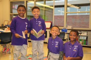 Four boys in purple School 2 shirts smile for the camera