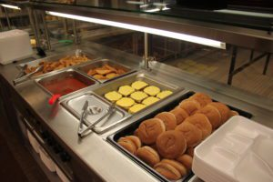 Hot food line with cheeseburgers and fries