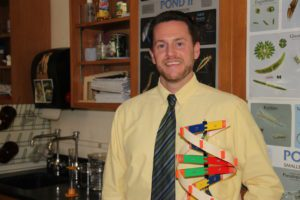 Justin Haviland in science classroom holding a model of a DNA strand