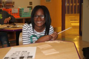 Girl smiles at camera while making a structure out of Popsicle sticks