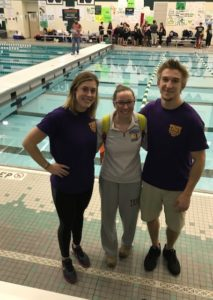 female swimmer with two coaches
