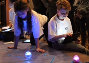 Male and female student demonstrate the use of robotics