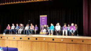 All 23 participants of the Spelling Bee sitting in chairs on the stage.