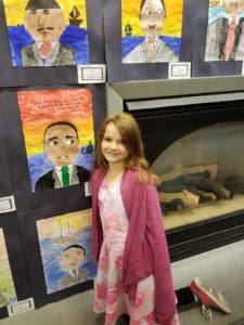 Students standing in front of their artwork.
