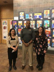 Teachers in front of art work