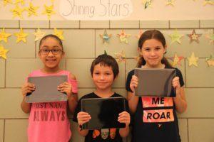 Three school 16 elementary students hold iPads