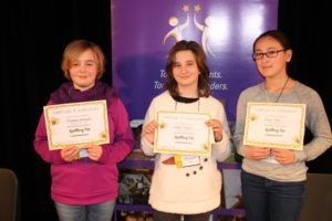 The three girls who won the spelling bee holding their certificates