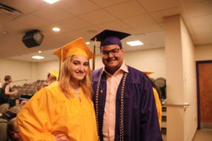 female student in yellow cap and gown with male student in purple cap and gown