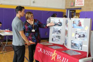 Woman at Questar III booth talking to a male student.