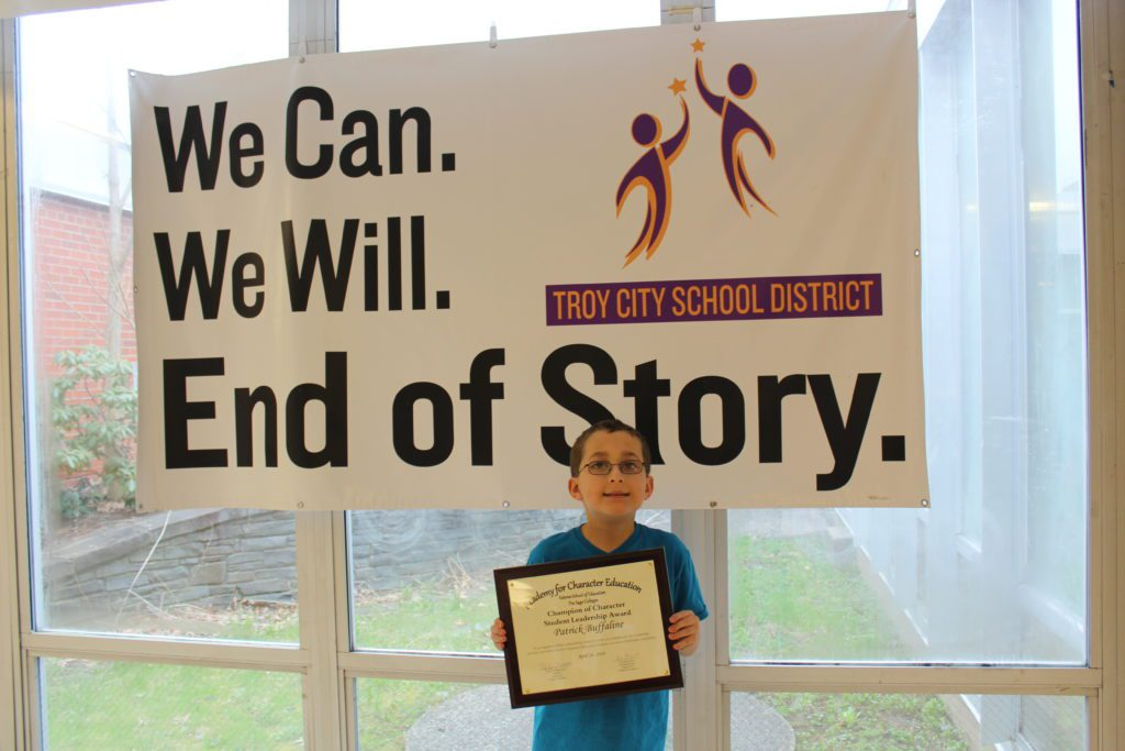 "Patrick holding his plaque in front of the Troy CSD ""We can, we will, end of story"" banner."