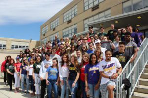 Group photo of seniors wearing their college shirts