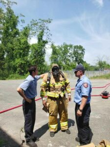 Firefighters and a student in fire gear