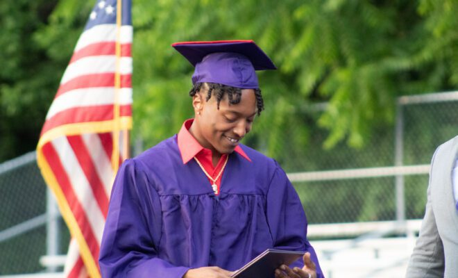 2021 students in yellow and purple cap and gown