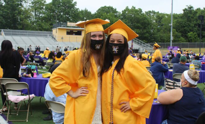 Two female graduates in yellow cap and gown